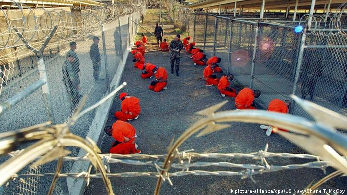 Prisoners in Gitmo wearing orange suits kneeling in two lines