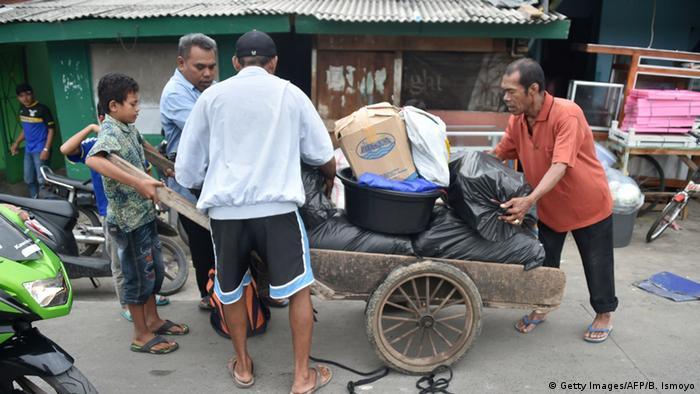 Indonesien Jakarta Männer packen Gepäck auf Handkarren