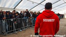 A member of the LAGeso security team watches over asylum-seekers queuing at the State Office of Health and Social Affairs (LAGeSo) registration centre in Berlin on December 10, 2015. The head of Berlin's main asylum seeker registration centre has been forced to resign over the chaos plaguing the office, which is struggling to process a record number of newcomers. AFP PHOTO / JOHN MACDOUGALL / AFP / JOHN MACDOUGALL (Photo credit should read JOHN MACDOUGALL/AFP/Getty Images) Copyright: Getty Images/AFP/J. MacDougall