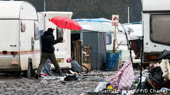 A man walks between trailers and tents in the 'Jungle'