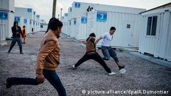 Children play soccer between containers