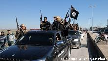 FILE - In this this file photo released on May 4, 2015, on a militant website, which has been verified and is consistent with other AP reporting, Islamic State militants pass by a convoy in Tel Abyad, northeast Syria. The Islamic State rakes in up to $50 million a month from selling crude from oilfields under its control in Iraq and Syria, part of a well-run oil industry that U.S. diplomacy and airstrikes have so far failed to shut down, according to Iraqi intelligence and U.S. officials.(Militant website via AP, File) Copyright: picture-alliance/AP Photo