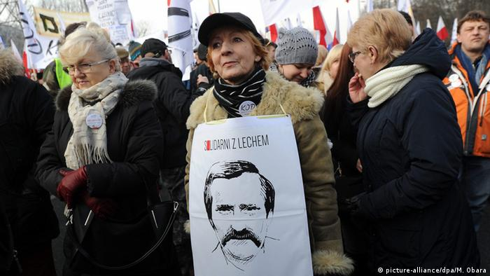 A woman holds a placard with a portrait of Lech Walesa and slogan Solidarity with Lech during a march organised by the Committee for the Defence of Democracy (KOD), in Warsaw, Poland, 27 February 2016.