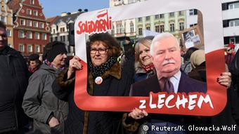 A woman with a cardboard cutout of former dissident, president and Nobel laureate Lech Walesa