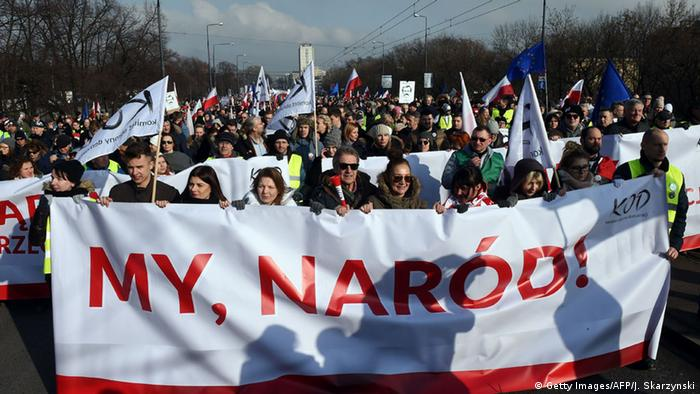 Thousands of Poles mach behind a banner that reads, We, The People