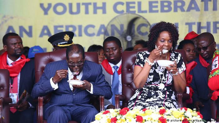President Mugabe and his wife Grace sit on a dais among Zimbabwean dignitaries