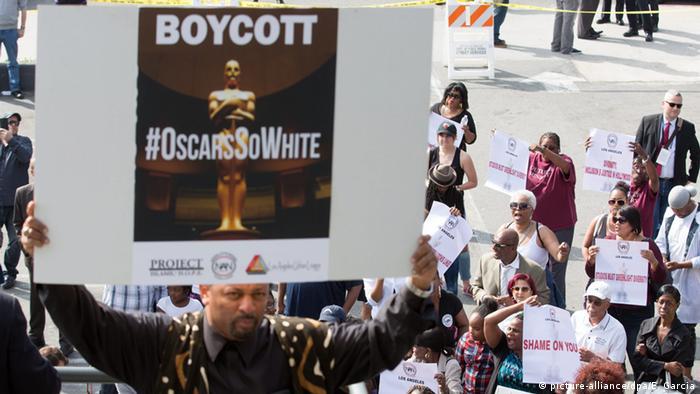 Ein Teilnehmer der Demo hält ein Schild hoch, auf dem unter dem Hashtag OscarsSoWhite zum Boykott der Preisverleihung aufgerufen wird
