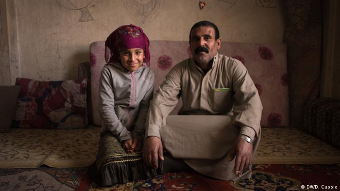 Dihal and his daughter sit on the floor in a run-down room