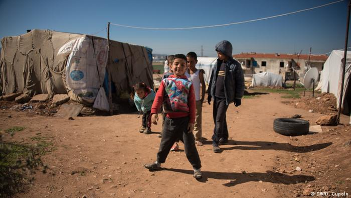 Children stand outside makeshift tents in Torbali