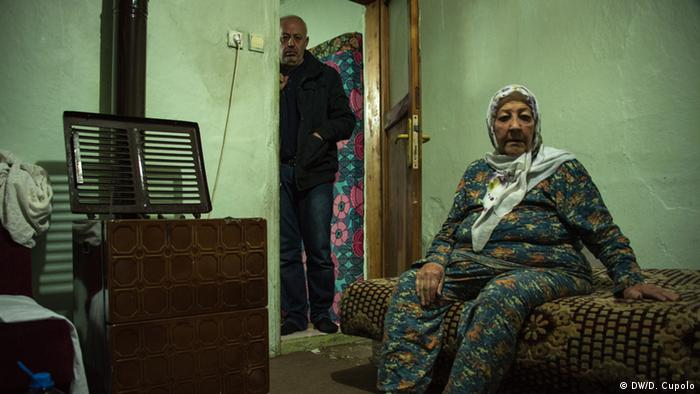 A woman sits on a bed in a rundown room, her husband stands in the door