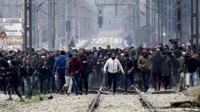 Hunderte Männer laufen die Bahntrasse Richtung mazedonischer Grenze entlang. (Foto: AP Photo/Boris Grdanoski)