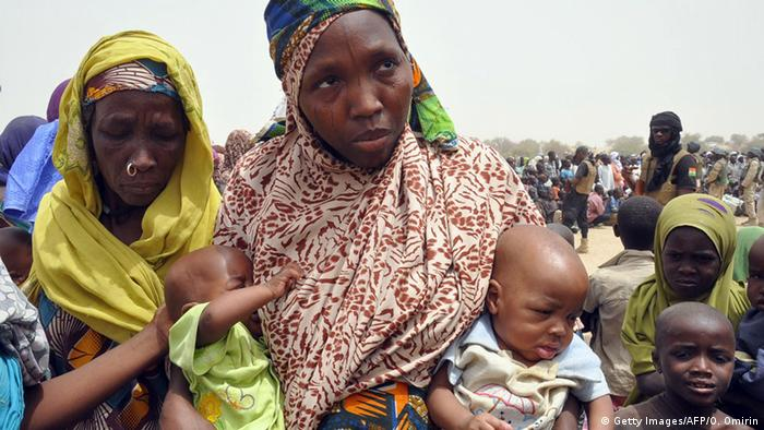 Nigerien woman with two small children under her arms