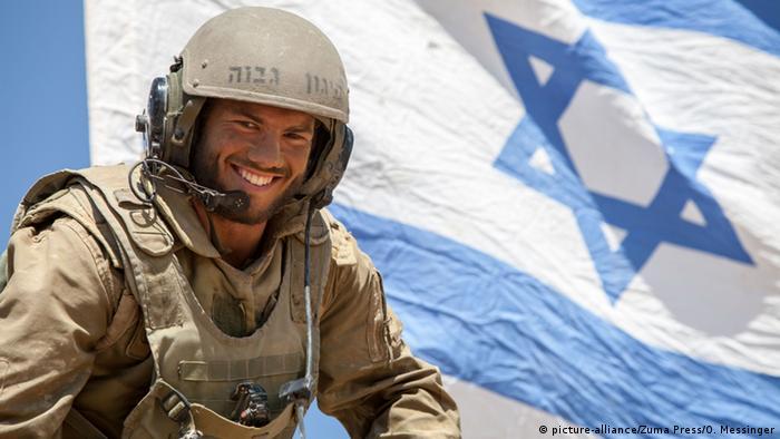 Soldado diante de bandeira de Israel