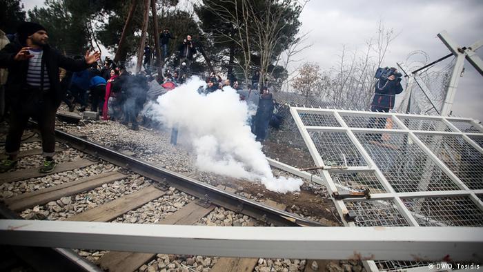 Über den Grenzzaun fliegen Kartuschen mit Tränengas auf protestierende Flüchtlinge. (Foto: DW/D. Tosidis)