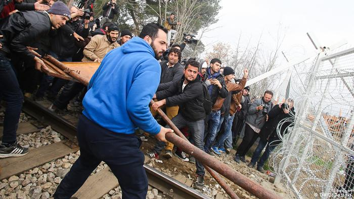 An der Grenze zwischen Griechenland und Mazedonien versuchen Flüchtlinge mit einem Rammbock den Grenzzaun niederzureißen. (Foto: DW/D. Tosidis)