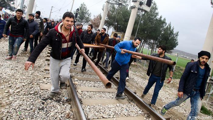 An der Grenze zwischen Griechenland und Mazedonien stürmen Flüchtlinge mit einem Rammbock entlang der Bahnschienen auf den Grenzzaun zu. (Foto: DW/D. Tosidis)