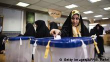 An Iranian woman casts her ballot to vote for both parliamentary elections and Assembly of Experts at a polling station at Massoumeh shrine in the holy city of Qom, 130 kms south of Tehran, on February 26, 2016 (Photo: BEHROUZ MEHRI/AFP/Getty Images)