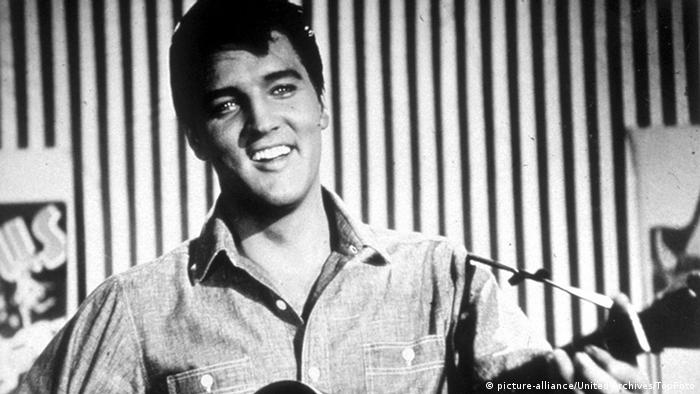 Elvis Presley laughs with a guitar in hand (picture-alliance/United Archives/TopFoto)