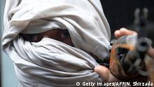 TOPSHOT - An Afghan former Taliban fighter carries his weapon before handing it over as part of a government peace and reconciliation process at a ceremony in Jalalabad on January 12, 2016. More than a dozen former Taliban fighters from Ghani district of Nangarhar province handed over their weapons as part of a peace reconciliation program. AFP PHOTO / Noorullah Shirzada / AFP / Noorullah Shirzada (Photo credit should read NOORULLAH SHIRZADA/AFP/Getty Images) Copyright: Getty Images/AFP/N. Shirzada