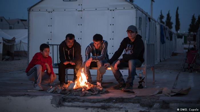 A group of Syrian refugees sits around a camp fire in Diavata refugee camp