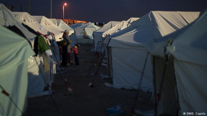 A woman stands with her son amid tents in Diavata refugee camp outside Thessaloniki