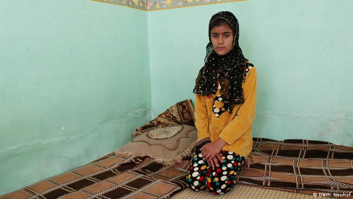 Thirteen-year-old Ariso sits on a carpet in her home