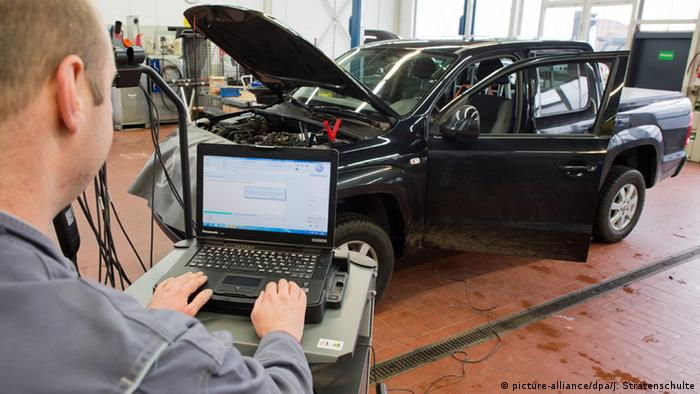 A picture of a mechanic checking data from a passenger car with a computer