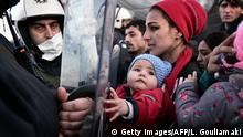 02.03.2016+++ A woman holds a baby as migrants and refugees stand facing Greek police while waiting to cross into Macedonia at the gate of the Greek-Macedonian border, near the Greek village of Idomeni, on March 2, 2016, where thousands of people are stranded. The EU on March 2 proposed 700 million euros in emergency aid for Greece and other states as it began to tackle the migrant crisis within its borders like humanitarian disasters in developing countries. The United Nations has warned of a looming humanitarian crisis as thousands of people remained stuck in miserable winter conditions on the Greece-Macedonia border after Balkans states and Austria capped the numbers arriving. / AFP / LOUISA GOULIAMAKI (Photo credit should read LOUISA GOULIAMAKI/AFP/Getty Images) +++ (C) Getty Images/AFP/L. Gouliamaki