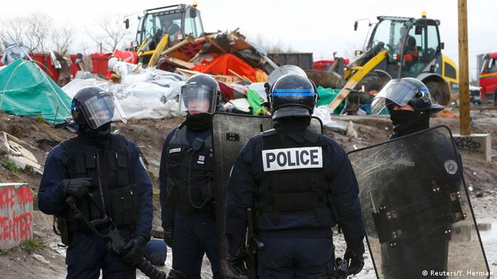 Police stand by as workers tear down refugee camp in Calais.