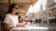 Mulher de óculos escuros sentada num café