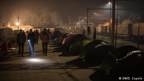 People walk past tents pitched next to a fence