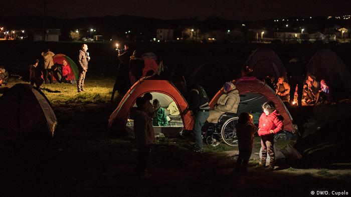 Adults and children stand outside of in tents on a field