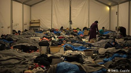 Rows of people lay in blankets and sleeping bags in a crowded group tent