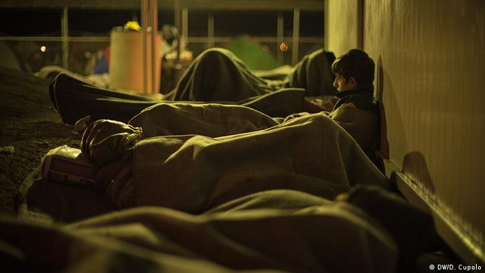 Three men lay outside wrapped in blankets in the dark