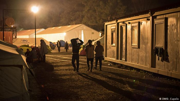 Three people walk between containers in the dark camp