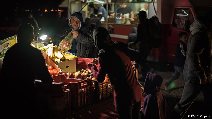 A man puts fruit in a sack for a nighttime customer in Idomeni