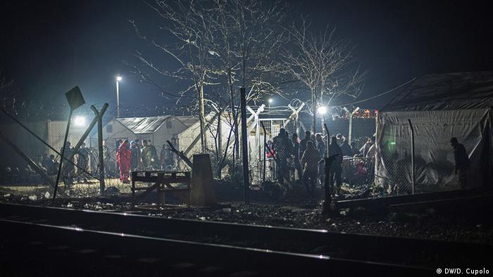People stand at the border crossing to Macedonia, which is lit by lanterns