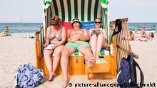 ARCHIV: 2015++++++Die Urlauber Elke Schneglsberg (l-r), Lothar Göwel und Pamela Schneglsberg liegen am 17.07.2015 in Timmendorfer Strand (Schleswig-Holstein) in einem XXL-Strandkorb, der Platz für drei Personen bietet. Foto: Daniel Bockwoldt/dpa (zu dpa Ein Platz an der Sonne - Urlauber lieben Strandkörbe vom 18.07.2015) +++(c) dpa - Bildfunk+++ (c) picture-alliance/dpa/D. Bockwoldt