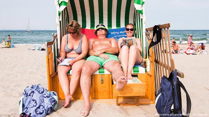 Three people in a beach chair (picture-alliance/dpa/D. Bockwoldt)