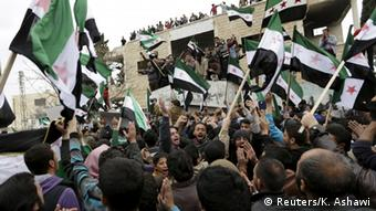 Syrian protesters carry Free Syrian Army flags and chant slogans during an anti-government protest.