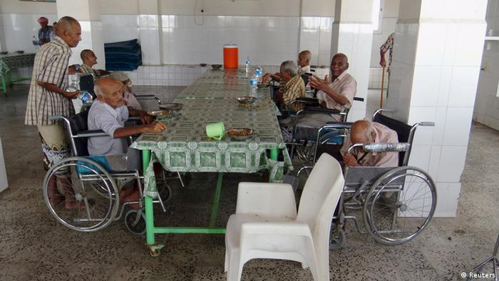 Survivors of the terror attack - all of them in wheel chairs - sit around a large table.