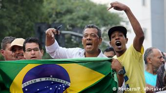 Protesters against Lula hold up a Brazilian flag