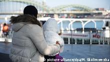 27.10.2015 *** ARCHIV - Eine Flüchtlingsfrau aus Nigeria sitzt am 27.10.2015 in Köln (Nordrhein-Westfalen) mit ihrer Tochter auf dem Schoß am Rheinufer. Flüchtlingsheime können vor allem Frauen und Kindern häufig keinen Schutz gegen Sexualverbrechen bieten. Foto: Monika Skolimowska/dpa (zu dpa/lnw: «Flüchtlingsheime bieten keinen Schutz vor sexueller Gewalt» vom 01.12.2015) +++(c) dpa - Bildfunk+++ Copyright: picture-alliance/dpa/M. Skolimowska