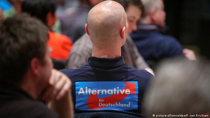 Ein glatzköpfiges Mitglied der Partei AfD mit Partei-T-Shirt sitzt im Publikum einer Wahlkampfveranstaltung