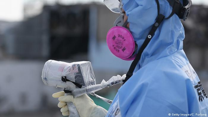 Japan Okuma Fukushima Daiichi Schutzanzug employee uses a a radiation dosage minitor (Getty Images/C. Furlong)