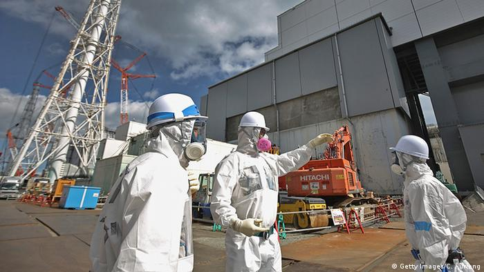 Fukushima workers in protective clothing stand outside reactor 4 as they continue the radiation decontamination process (Photo: Getty Images/C. Furlong)
