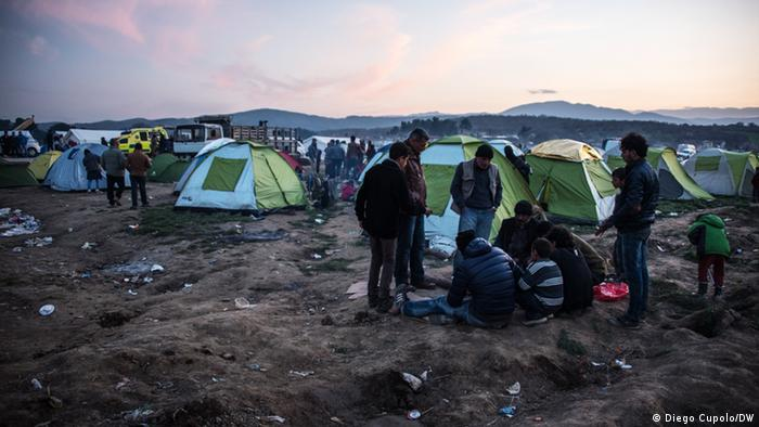 A group of men start a camp fire in Idomeni refugee camp