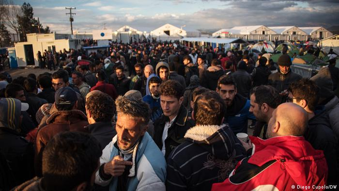A man tries to hold his place towards the end of the food line amid a sea of people in Idomeni refugee camp