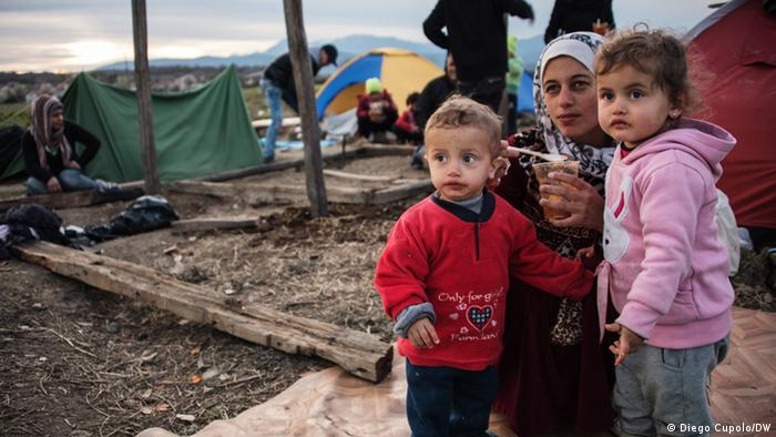 A Syrian mother feeds her children as her husband builds a makeshift shelter in Idomeni refugee camp.