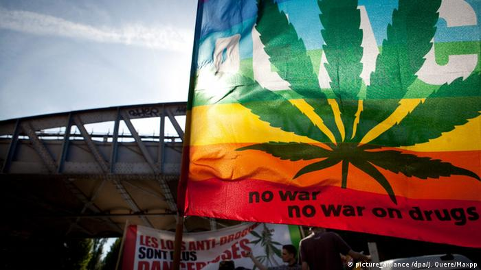 A flag carried during a global marijuana march says No war, no war on drugs and features a large marijuana leaf.